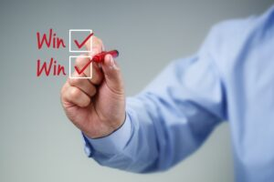 Checklist on glass with businessman hand drawing win-win