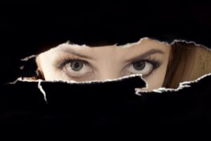 Woman's eyes spying through a hole